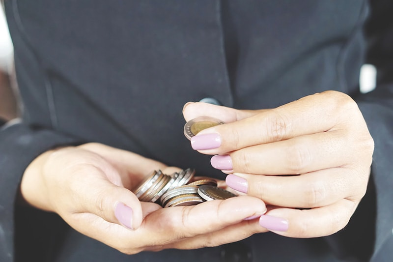 A woman counting coins in her hands | How Can I Afford a New AC System (and Other HVAC Equipment)? | Afford New HVAC Financing