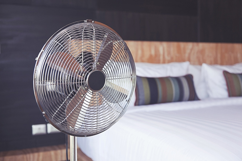 Old electric fan near the bed in the room improving indoor air quality