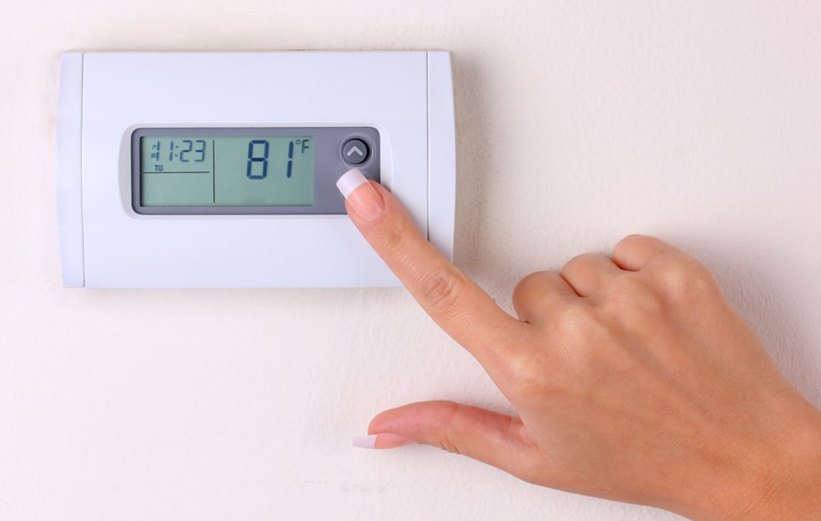 thermostat. woman's hand setting the room temperature on a modern programmable wall heater. closeup