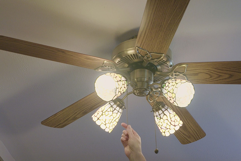 Person turning on their ceiling fan in order to save energy