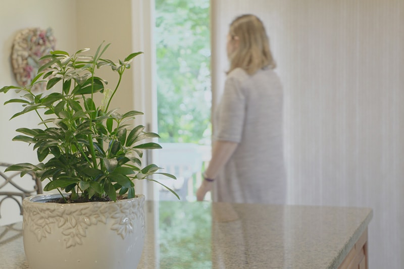 woman closing her blinds to save energy